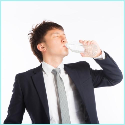 水を飲むスーツを着た若い男性