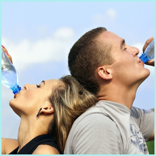 背中合わせに水を飲むカップル